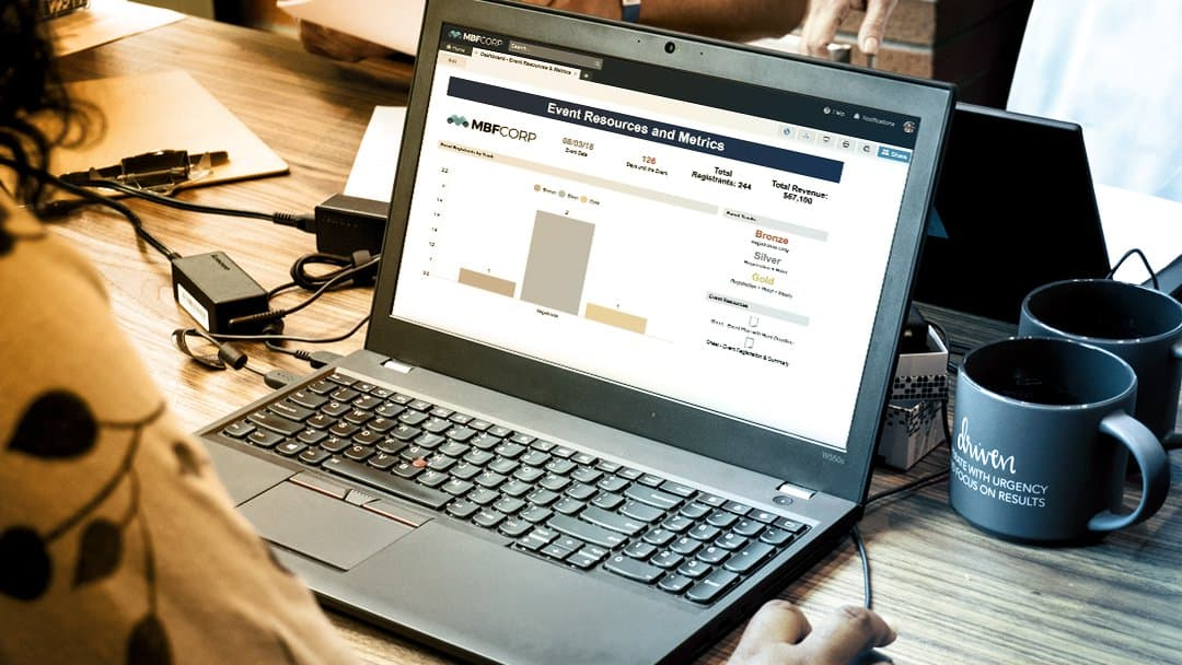 An office worker reviews a Smartsheet events dashboard on her laptop