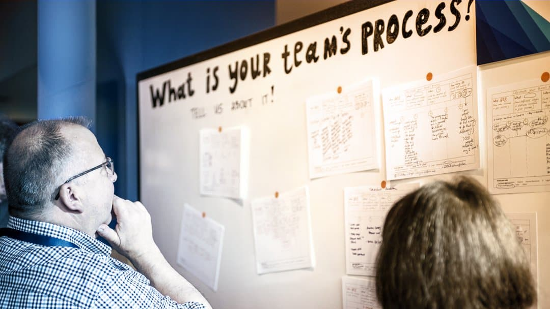 """A man looks at a whiteboard that reads """"What's your team's process?"""""""