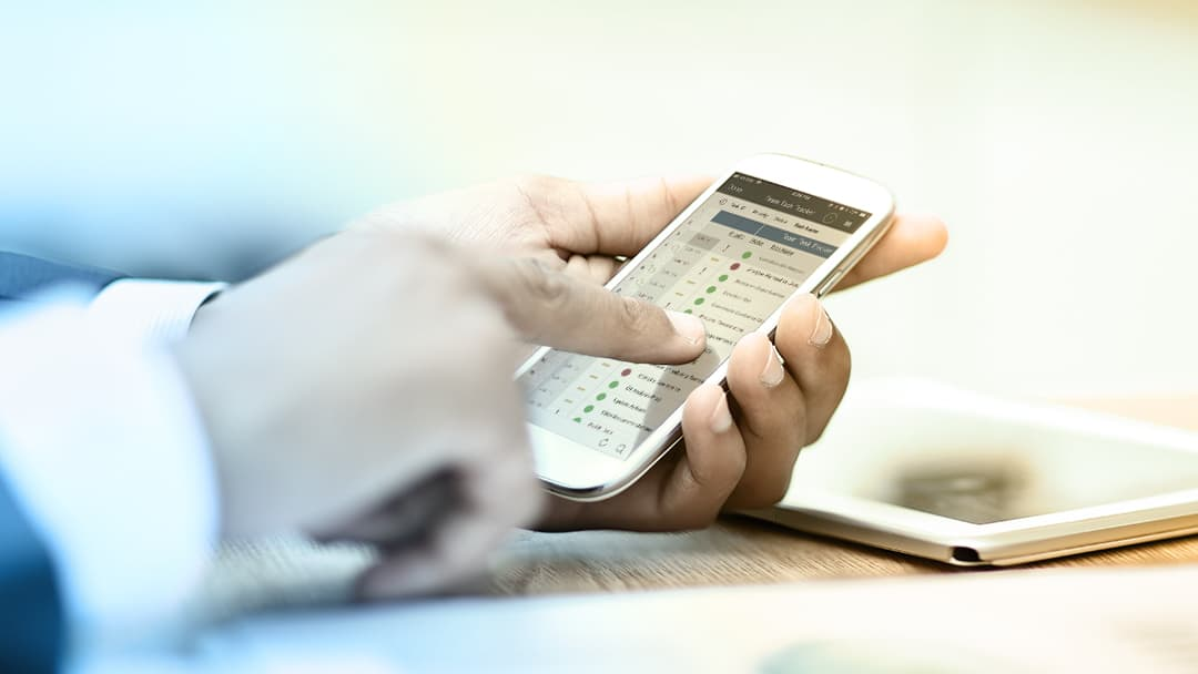 A businessman uses the Smartsheet mobile app on a smartphone.