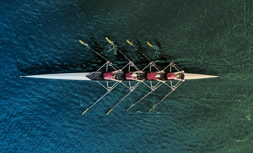 Overhead view of women's rowing team on blue water.