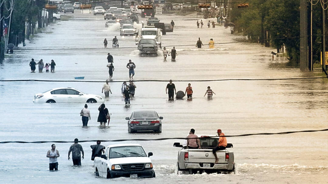 People standing amongst cars on a flooded Houston street.
