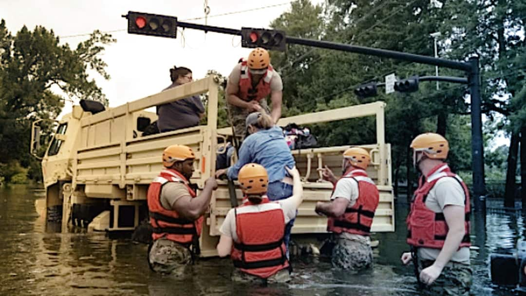 Volunteers help a woman into the bed of a truck on a flooded street.